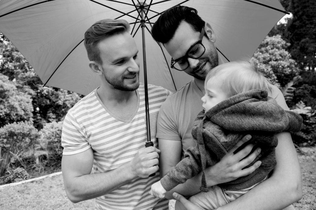pareja gay sonriendo con su hijo